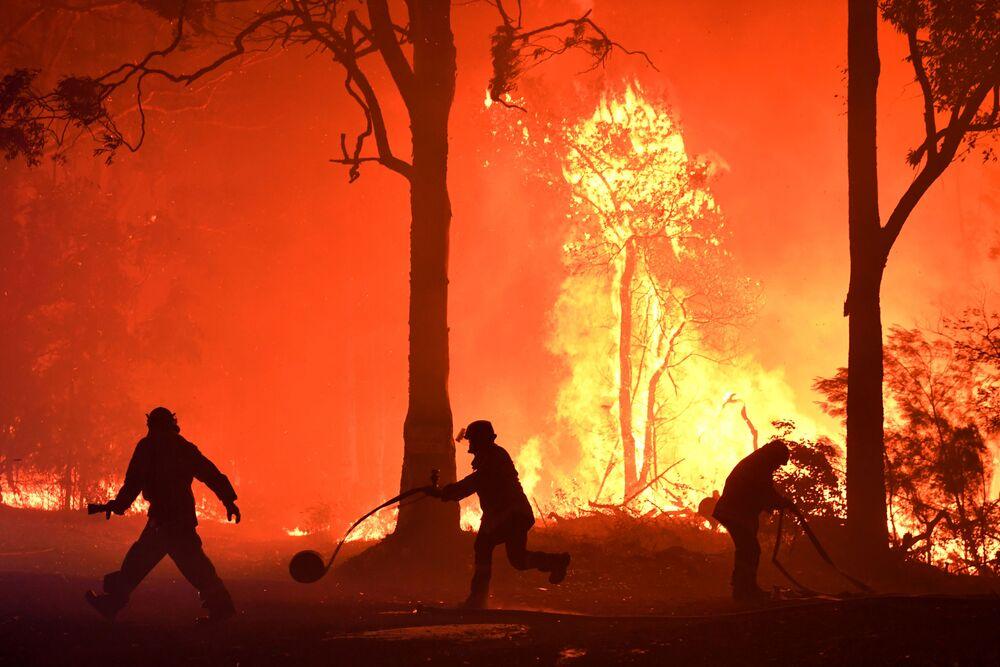 Voluntários, bombeiros e socorristas da Nova Gales do Sul lutam contra incêndio perto do povoado de Termeil, Austrália