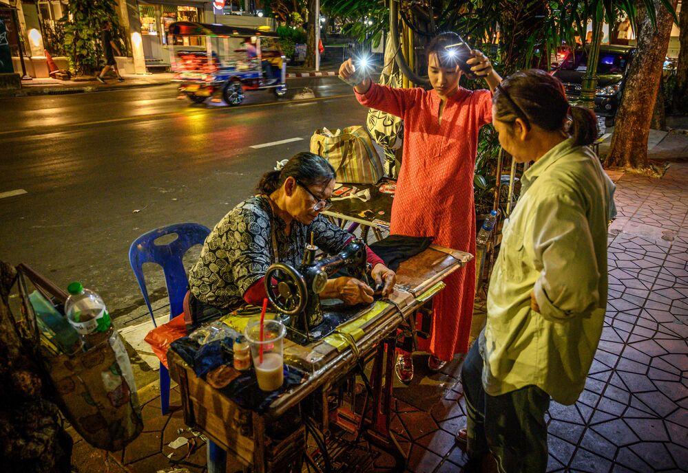 Mulher ilumina com celulares o local de trabalho de uma costureira de rua em Bangkok, Tailândia