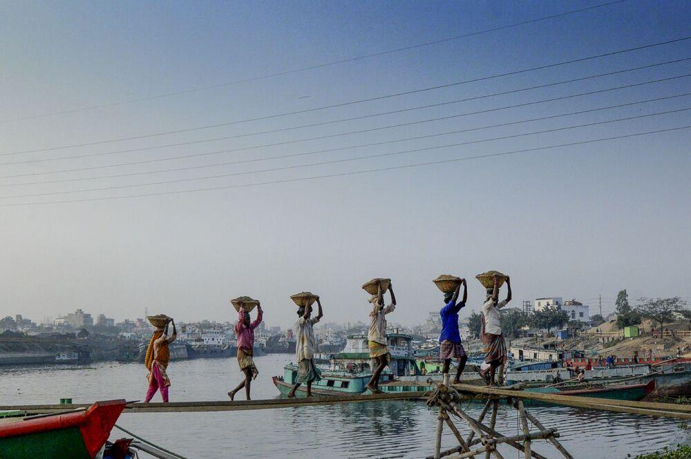 Homens transportam carga em cestas sobre suas cabeças na cidade de Daca, Bangladesh