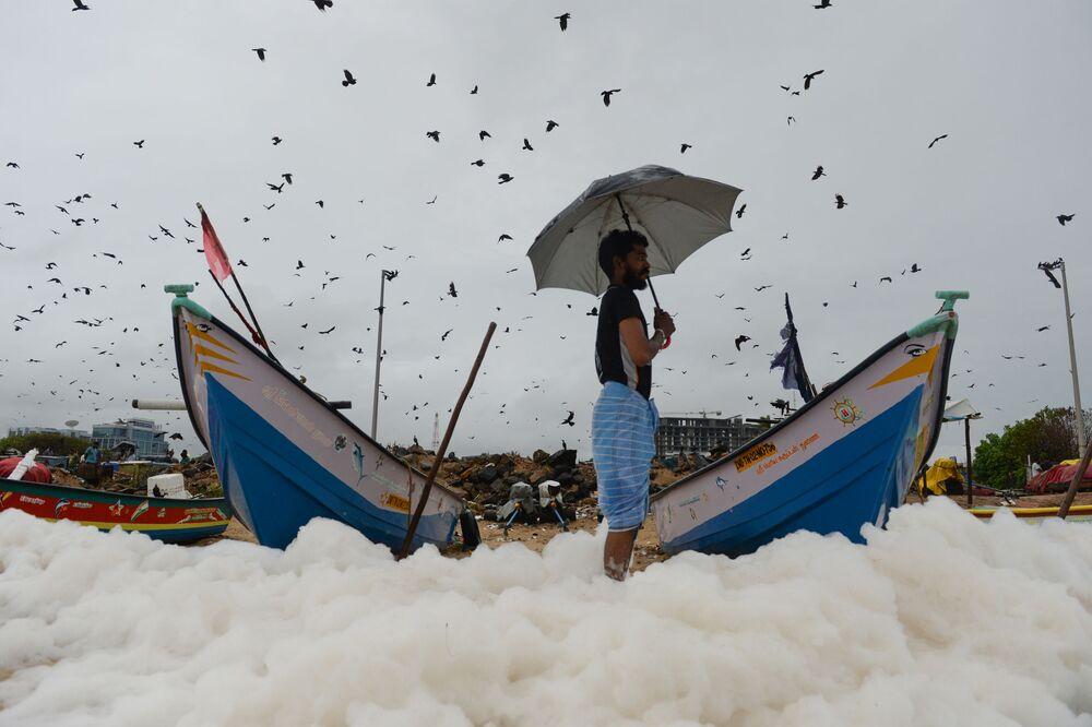 Homem em uma praia com espuma tóxica na Índia