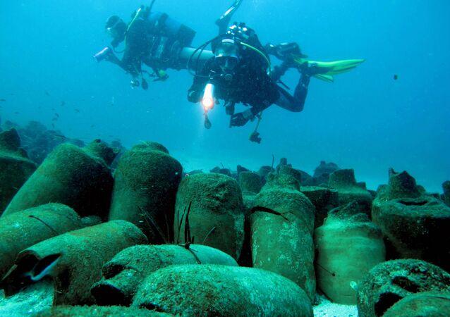 Mergulhadores observam antigos vasos romanos debaixo da areia