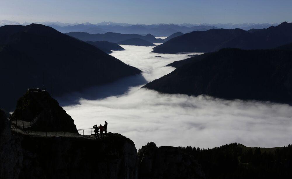 Vale tomado por nevoeiro e sendo visto dos Alpes, Alemanha