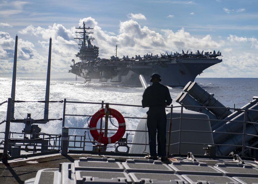 Marinheiro observa o porta-aviões USS Ronald Reagan e a fragata USS Chancellorsville.  Para a revista National Interest, a Marinha dos Estados Unidos seria atualmente a mais poderosa a navegar pelos mares.