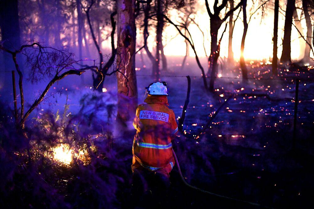 Bombeiro usando técnica para mudar a direção do fogo durante incêndio na Austrália