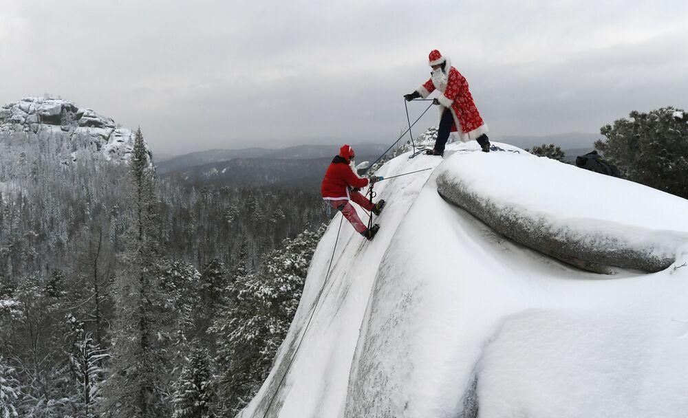 Dois homens de uma organização de busca e salvamento, um vestido de Papai Noel russo e outro de Santa Claus treinam escalada de rochedo na região russa de Krasnoyarsk