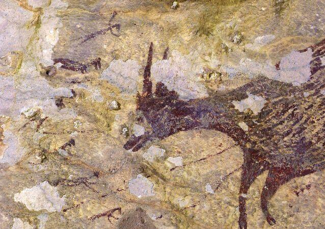 Uma pintura de caverna, que remonta a quase 44.000 anos, à vista em Leang Bulu Sipong 4, uma caverna de calcário em Sulawesi do Sul, Indonésia
