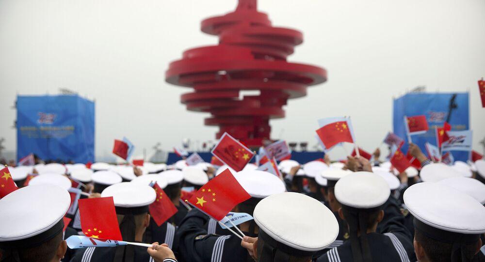Marinheiros seguram bandeiras da China durante parada naval