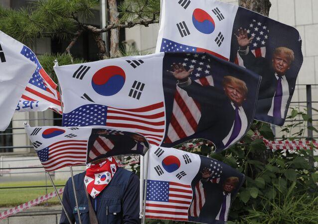 Homem vende bandeiras da Coreia do Sul, dos Estados Unidos e de Donald Trump (foto de arquivo)