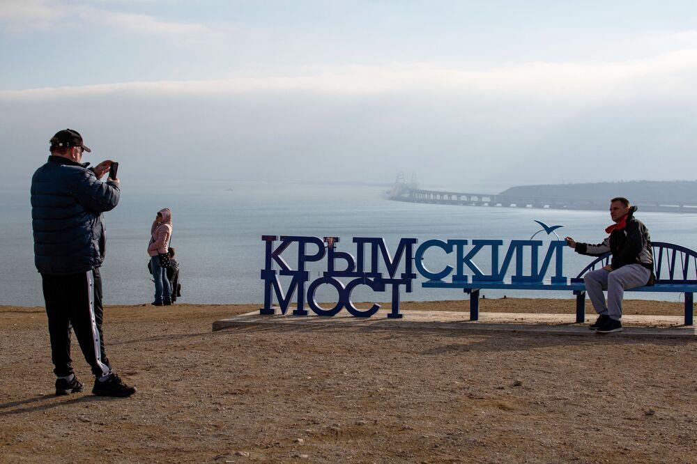 Pessoas fazendo fotos em frente à Ponte da Crimeia