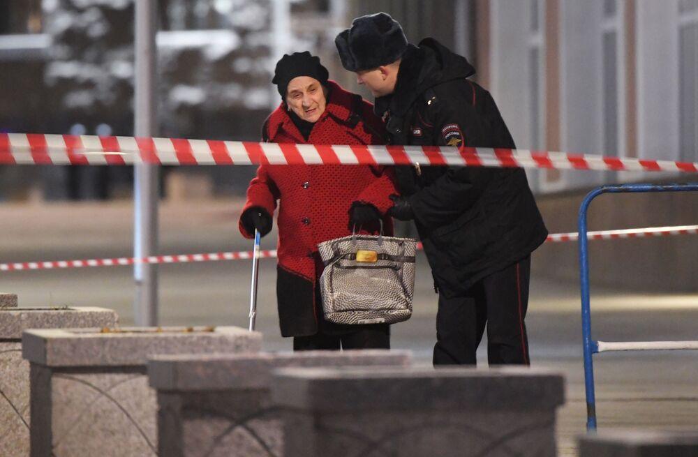 Um policial ajuda uma mulher a passar em uma zona do cordão de isolamento do prédio da FSB no centro da capital russa