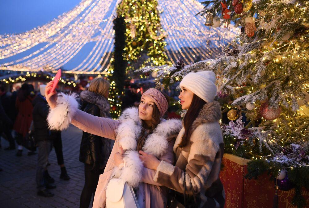 Jovens tiram selfies no festival Viagem ao Natal no centro de Moscou, Rússia