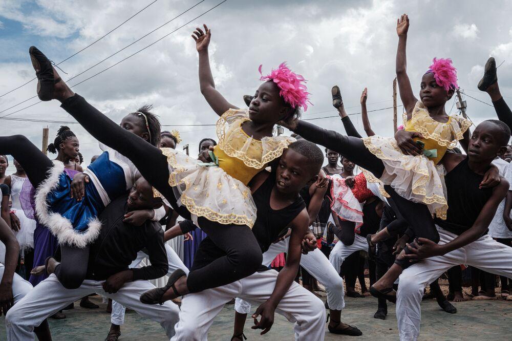 Participantes do Projeto Elimu dançam nas favelas de Kibera em Nairóbi, Quênia