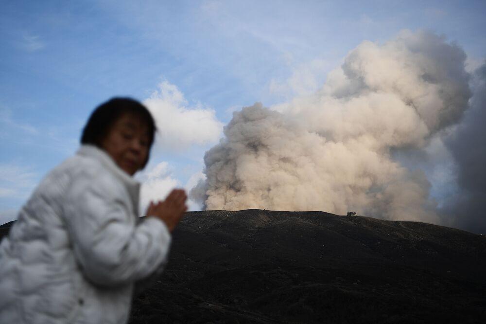Mulher posa perto de vulcão ativo na cidade de Aso, Japão