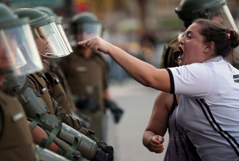 Mulher grita com policiais chilenos