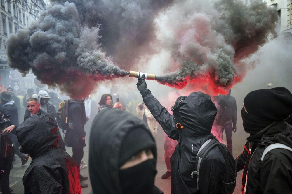 Manifestante com foguete na mão durante uma ação de protesto em Lyon, França