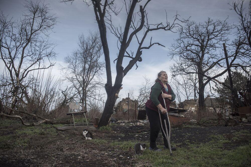 Moradora local perto das ruínas de um edifício na região de Donetsk