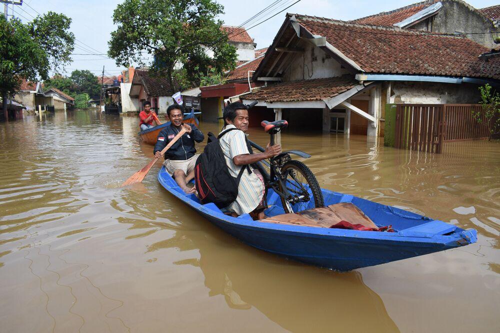 Pessoas passando de barco por uma estrada inundada na Indonésia