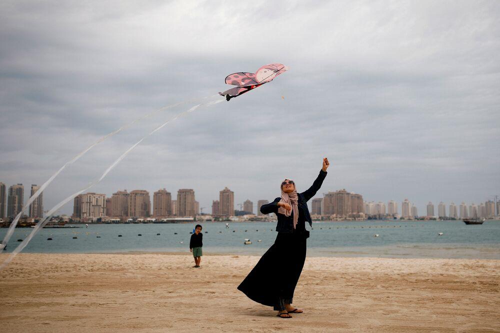 Mulher com traje muçulmano e uma pipa na praia em Doha, Qatar