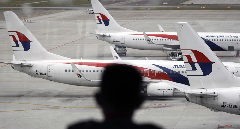 Homem olhando para aviões da Malaysia Airlines no aeroporto de Kuala Lumpur (foto de arquivo)