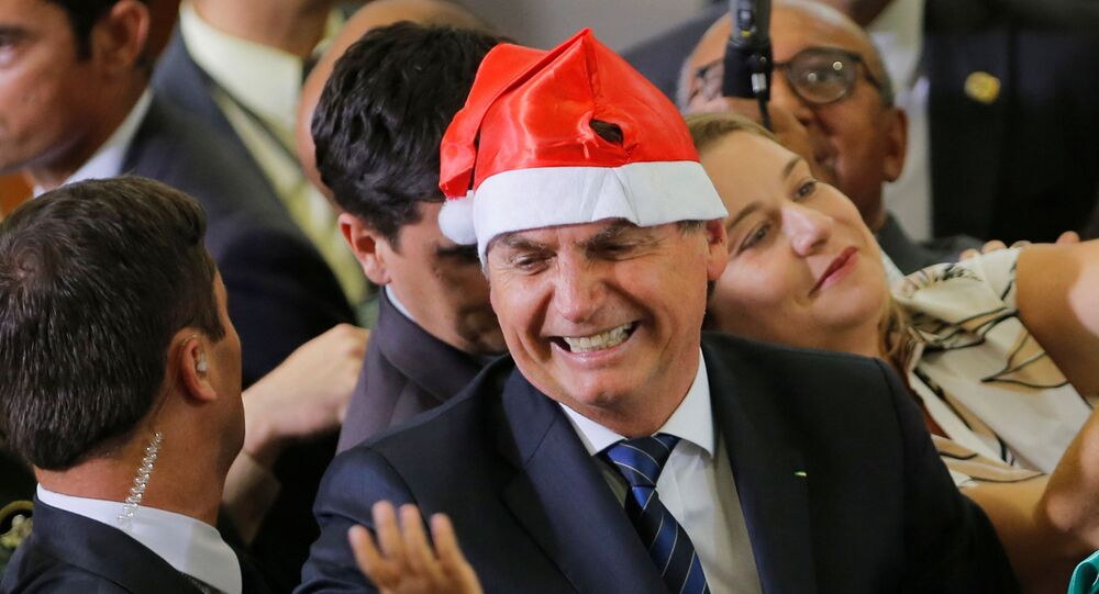 Presidente Jair Bolsonaro veste um adereço de Natal durante cerimônia no Palácio do Planalto