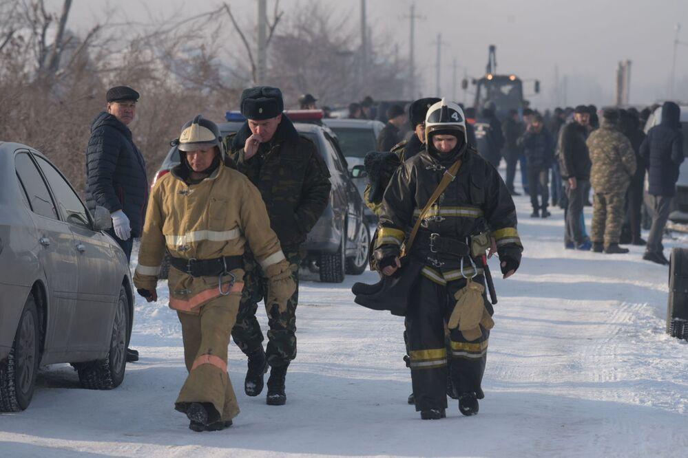 Equipe do serviço de emergência cazaque caminha perto do local do acidente aéreo no Cazaquistão, 27 de dezembro de 2019