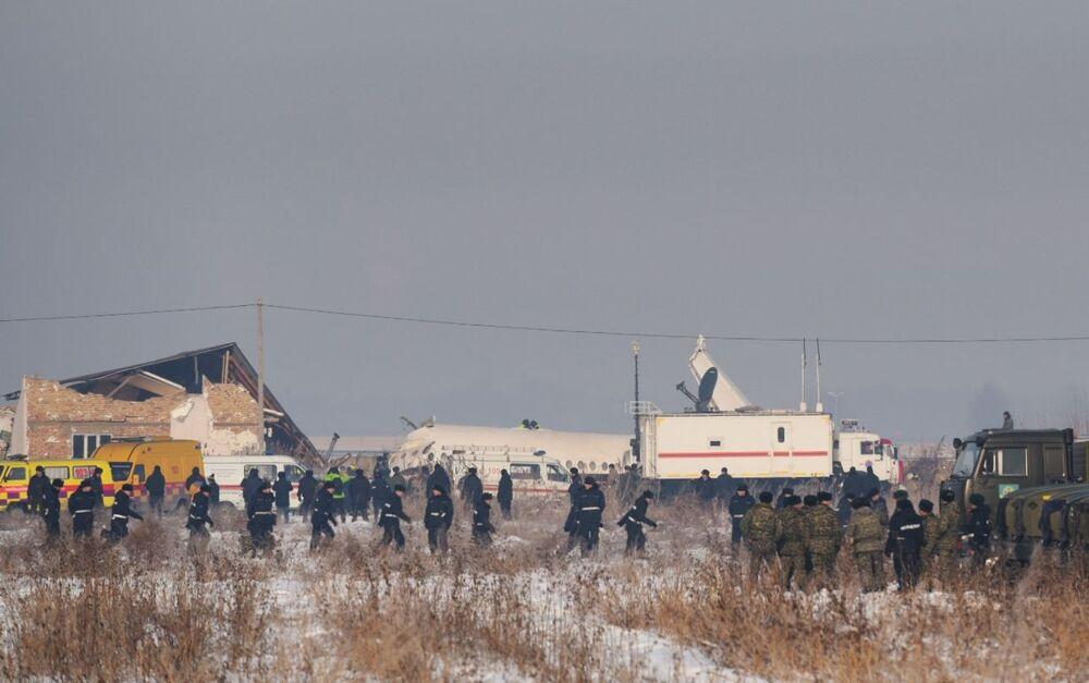 Equipe formada por polícias e serviços de emergência vasculha local da queda do avião cazaque Fokker 100