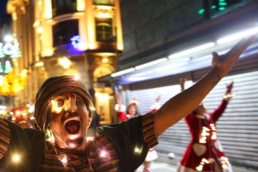 Homem vestido de Pinóquio em carnaval natalino na cidade de São Paulo