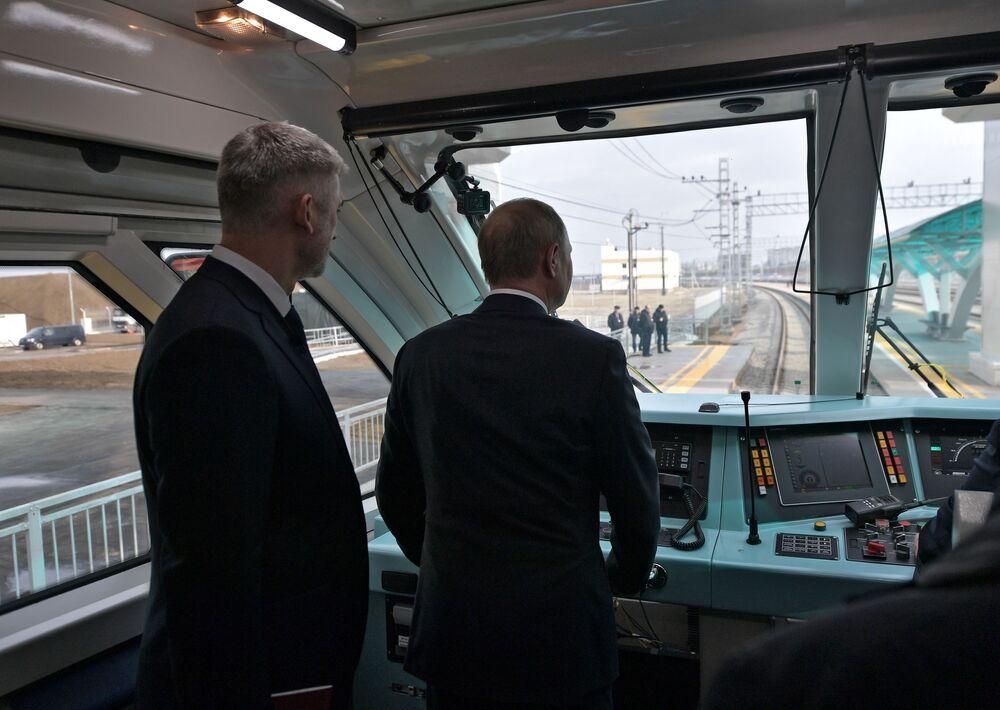 Presidente da Rússia, Vladimir Putin, na cabine do maquinista do primeiro trem a passar na linha ferroviária da Ponte da Crimeia, na Rússia