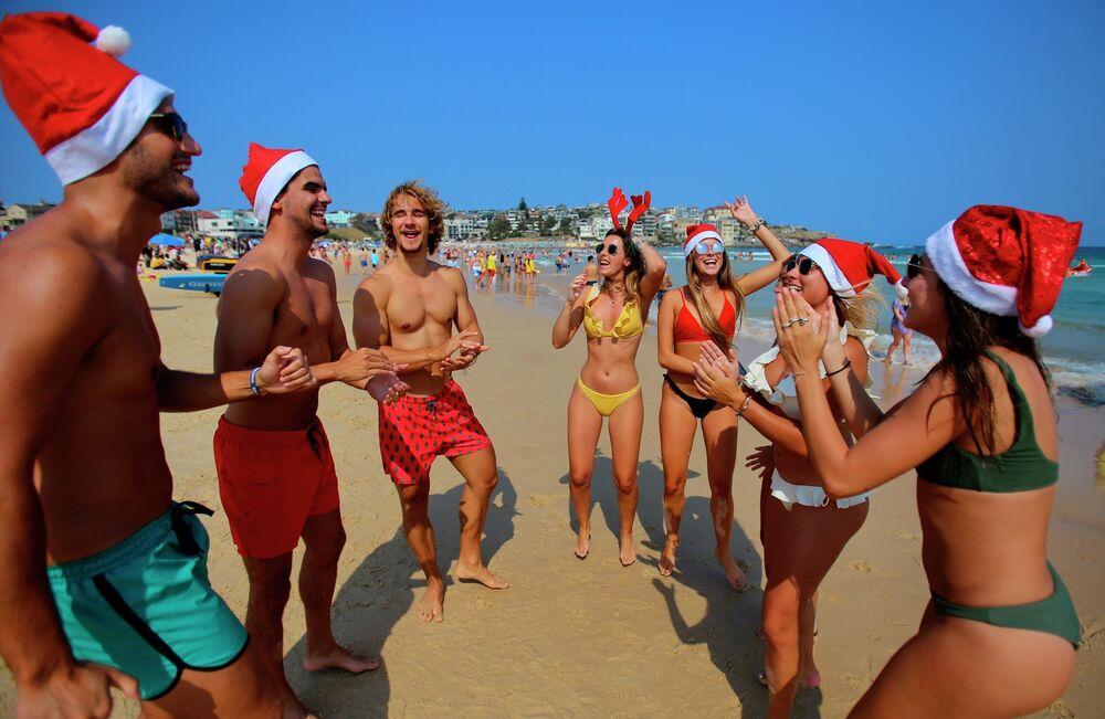 Turistas com trajes natalinos em uma praia de Sydney, Austrália
