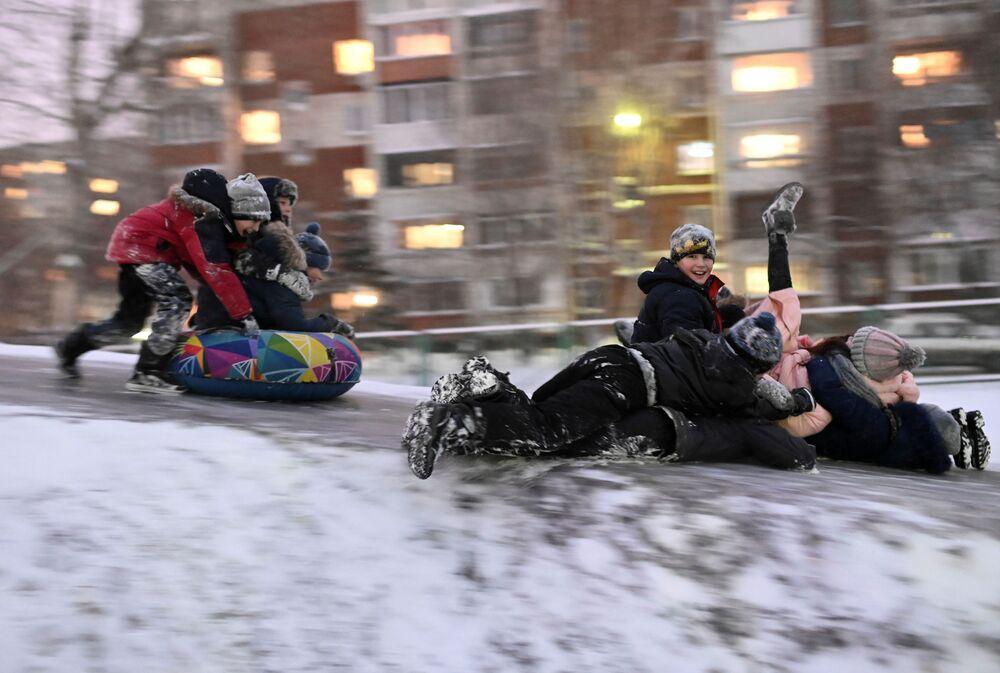 Crianças deslizam sobre gelo em boia de neve na cidade russa de Omsk