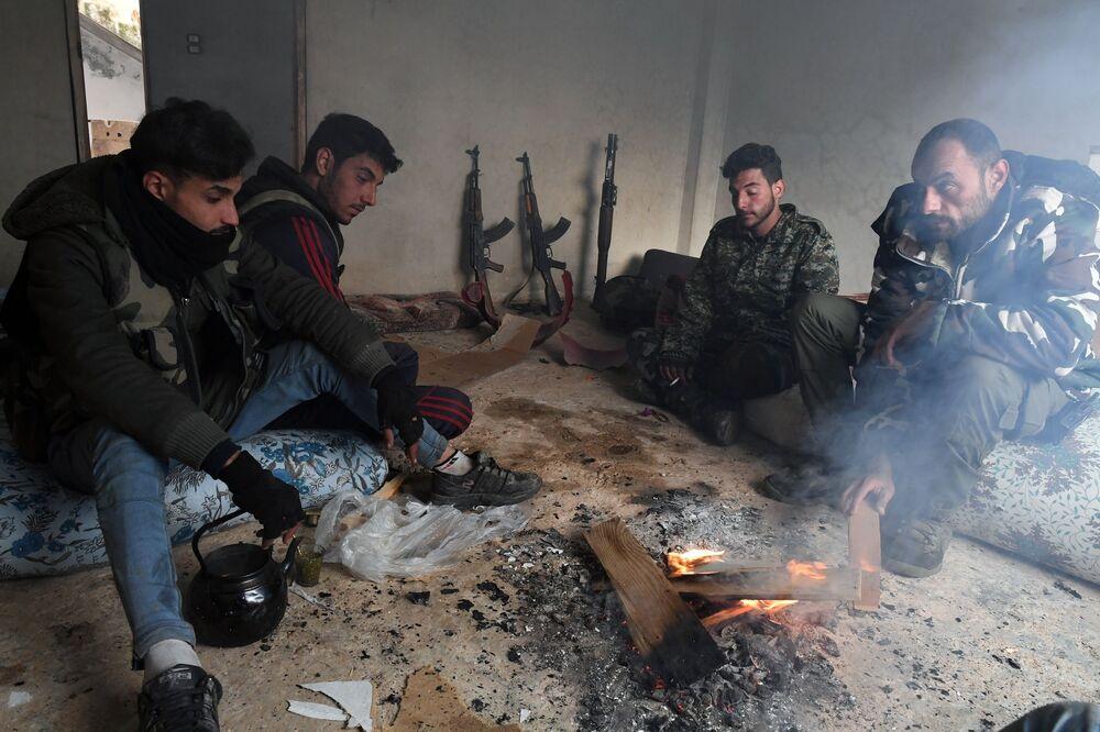 Milicianos sírios descansando após a libertação do vilarejo de Sukeya, na província síria de Idlib