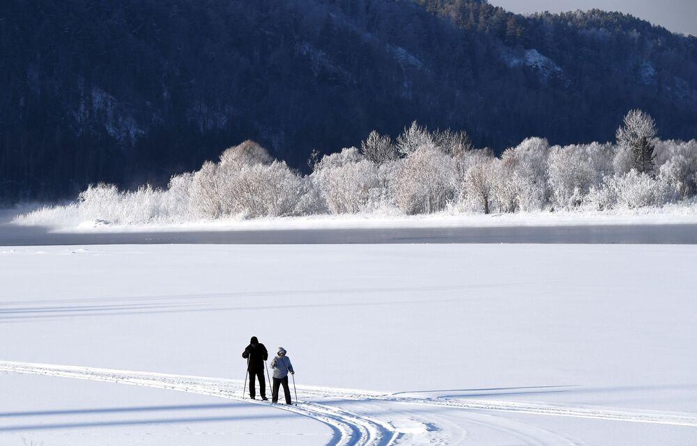 Duas pessoas passeiam de esqui na margem do rio Yenisei, próximo ao vilarejo de Ust-Mana, na região russa de Krasnoyarsk