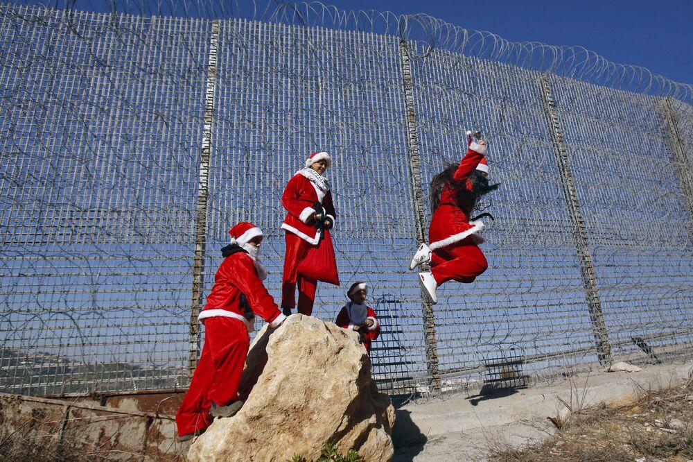 Palestinos vestidos de Papai Noel pulando de uma pedra ao lado de uma cerca com arame farpado de uma barreira de segurança feita por Israel perto do vilarejo de Wallajeh