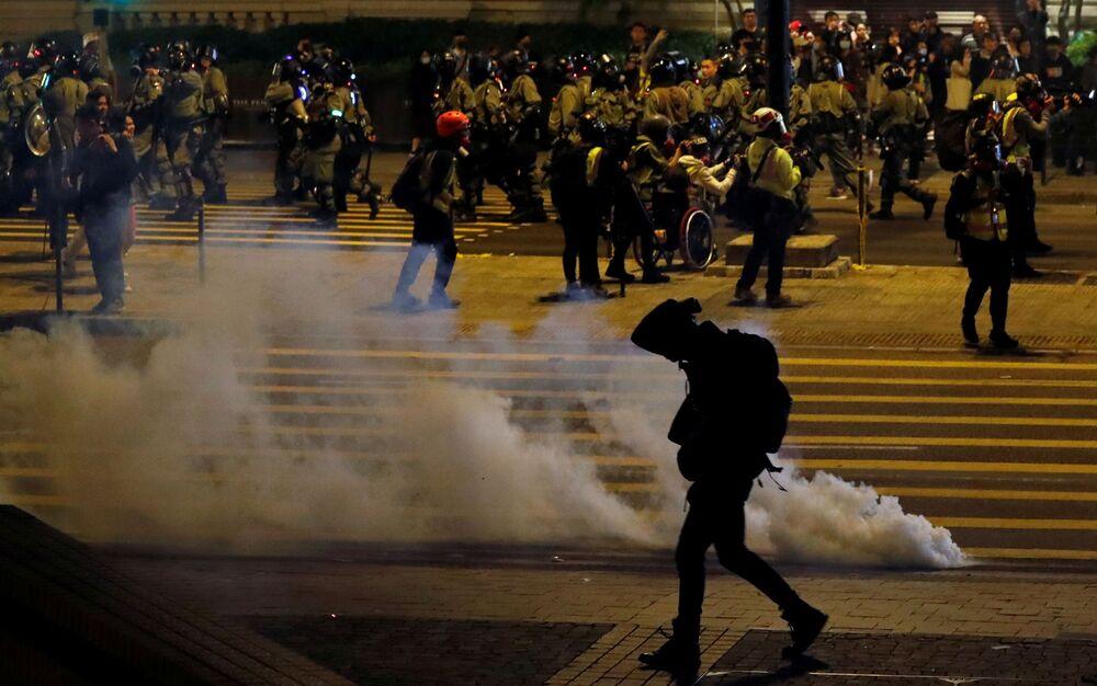 Manifestante antigovernamental passa ao lado de uma bomba de gás lacrimogênio na véspera de Natal em Hong Kong, China