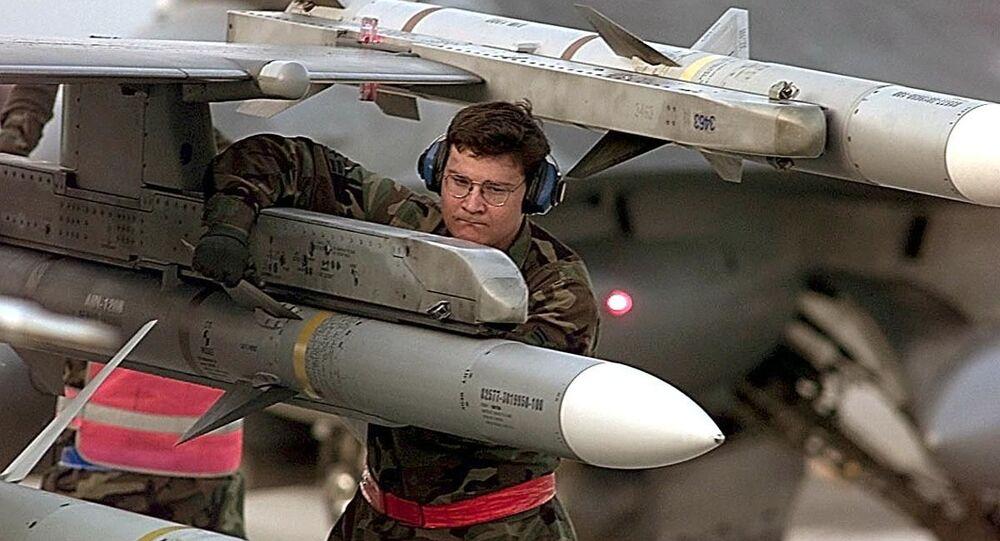 Militar dos EUA faz checagem final de míssil AIM-120, carregado na asa de um caça F-16 (foto de arquivo)