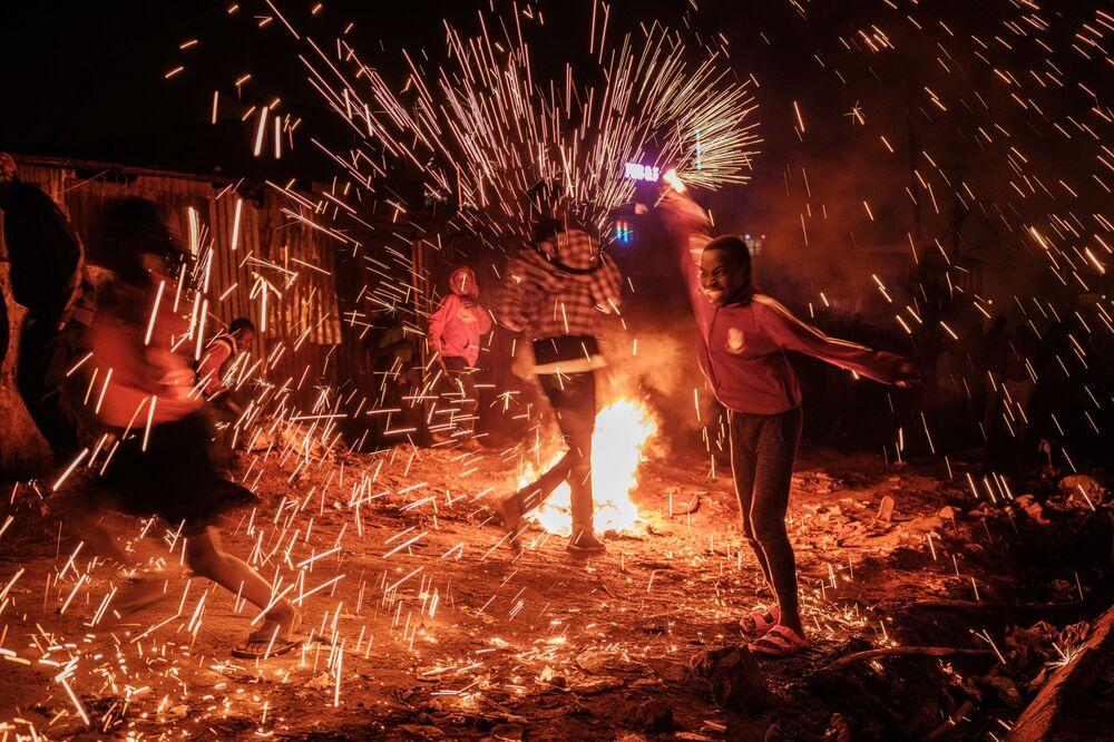 Menina girando palha de aço pegando fogo em Nairóbi, capital do Quênia