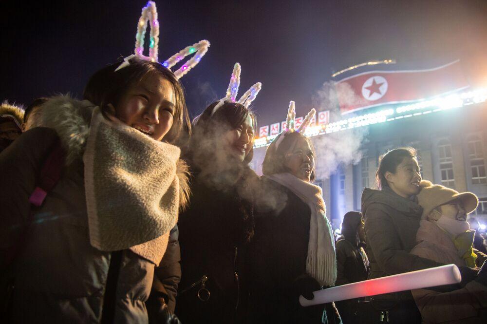 Jovens assistindo fogos de artifício nas celebrações do Ano Novo na praça Kim Il-sung em Pyongyang, Coreia do Norte
