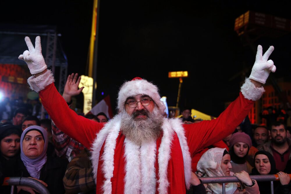 Manifestante antigovernamental vestido de Papai Noel nas celebrações da virada do ano da Praça dos Mártires no centro de Beirute, Líbano