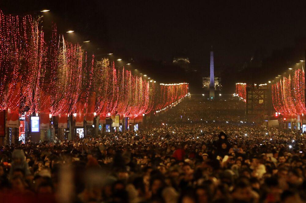 Pessoas em Paris assistindo a queima de fogos sobre o Arco do Triunfo