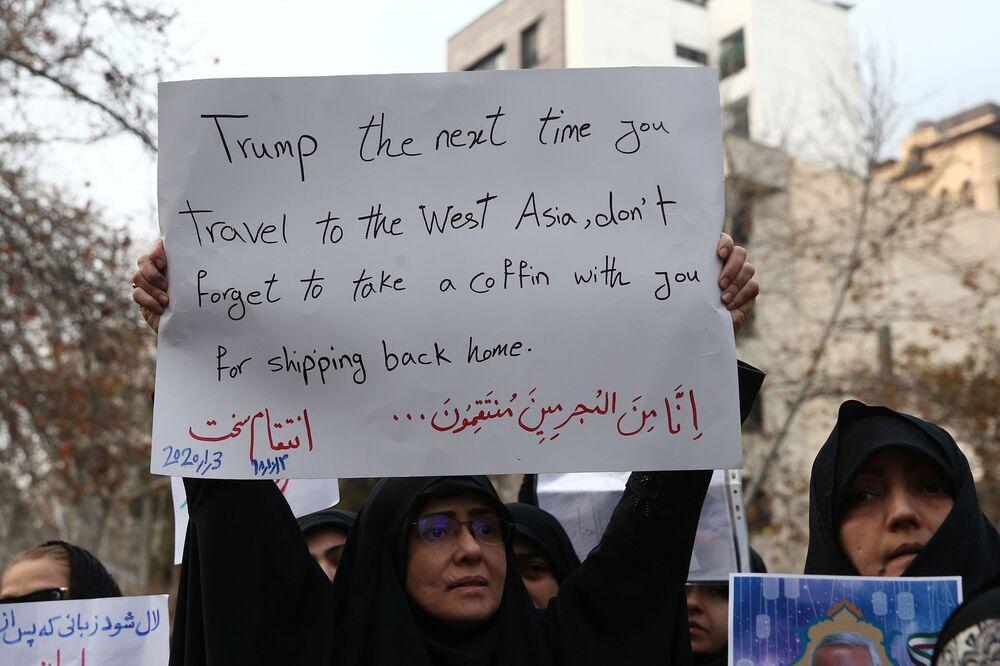 Manifestante iraniana segura cartaz sugerindo que Trump leve consigo um caixão na próxima vez que viajar ao Oriente Médio