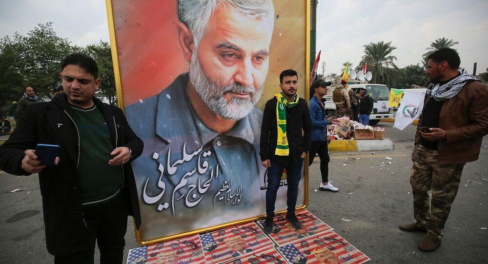 Militantes ao lado de quadro com o rosto do general iraniano Qasem Soleimani durante seu funeral