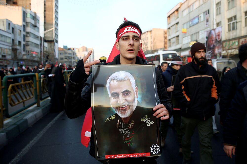 Homem leva retrato de Qassem Soleimani em cortejo fúnebre em Teerã, Irã
