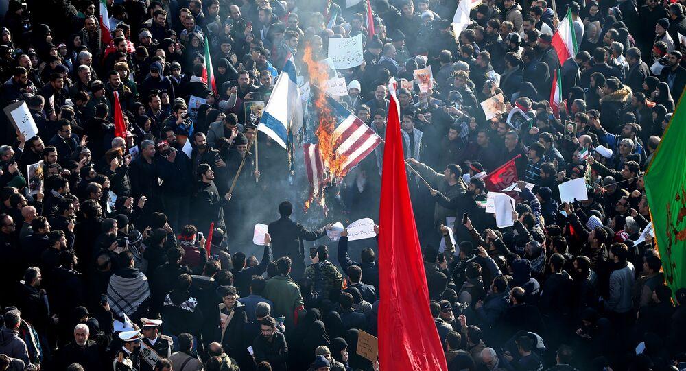 Bandeiras dos Estados Unidos e de Israel sendo queimadas por participantes do funeral do major-general iraniano Qassem Soleimani