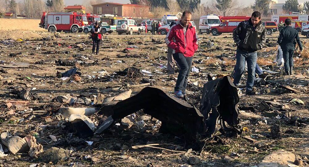 Pessoas observam os restos do avião ucraniano do voo PS752, que caiu perto do Aeroporto Internacional Imã Khomeini em Teerã, Irã