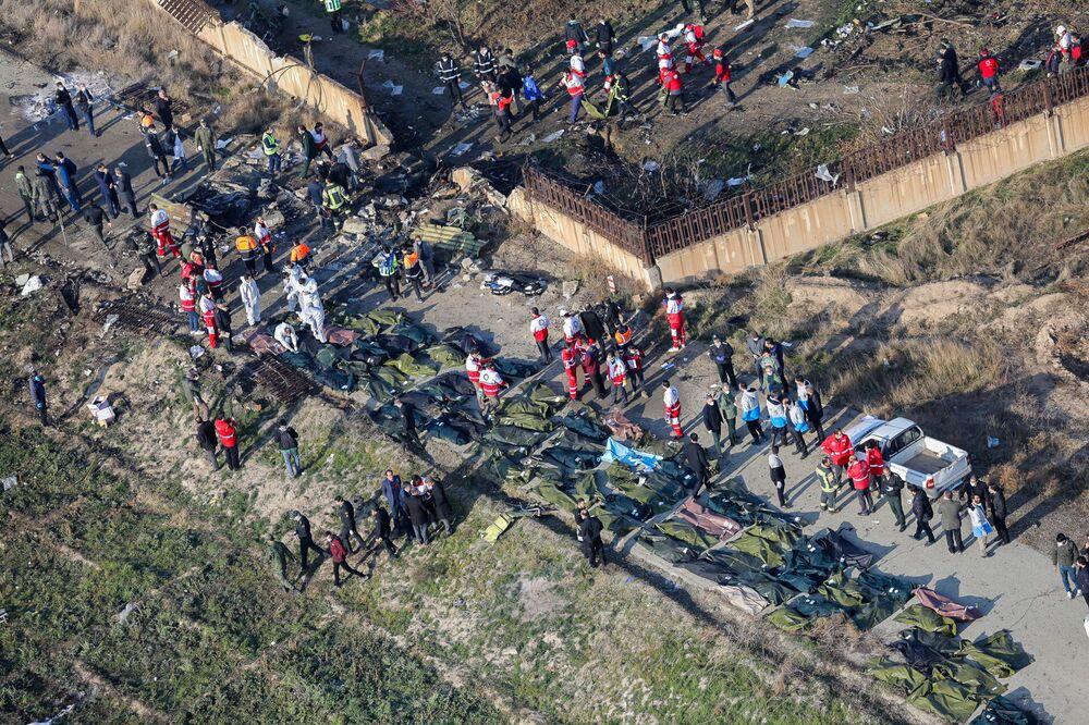 Equipes de resgate e moradores locais são fotografadas entre os corpos das vítimas da queda do voo PS752 Teerã-Kiev