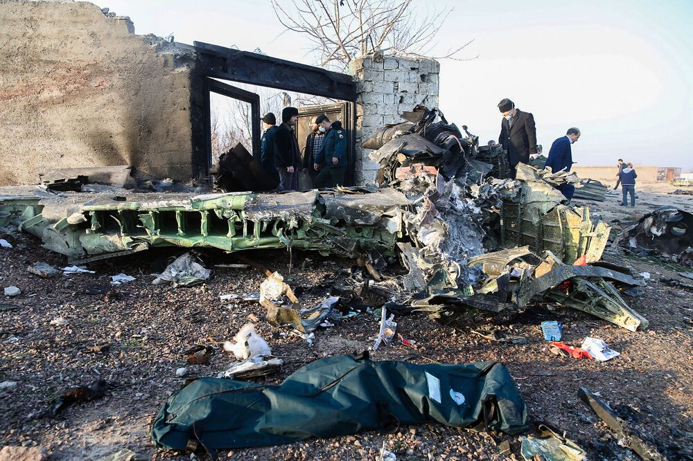 Pessoas observam destroços do Boeing 737 do voo PS752 Teerã-Kiev no local da queda do mesmo próximo do Aeroporto Internacional Imã Khomeini na capital iraniana, Teerã