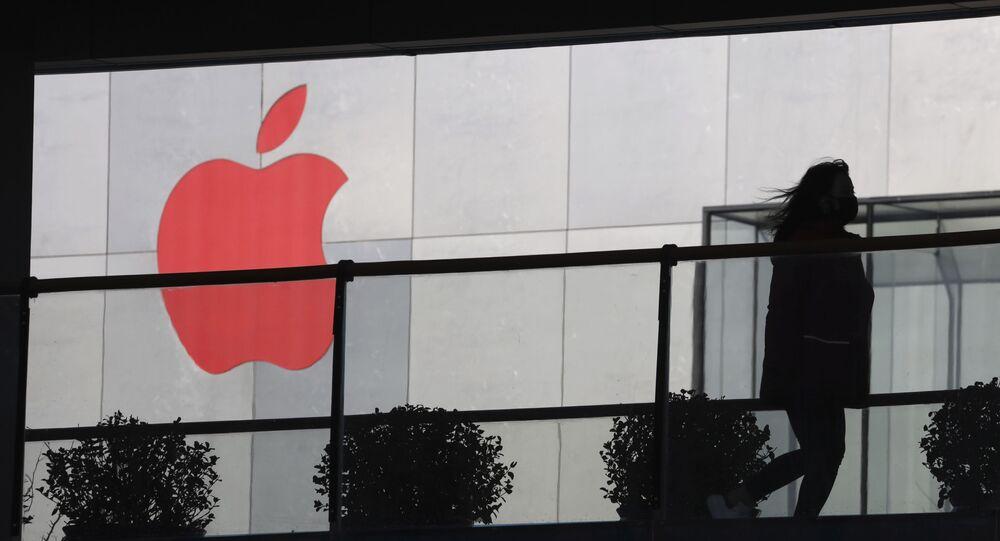 Mulher passando por logotipo vermelho da Apple em Pequim, China