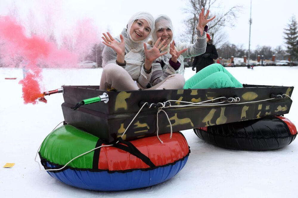 Vencedoras de festival de descida em boia de neve, fantasiadas de múmias, na cidade de Kazan, Rússia