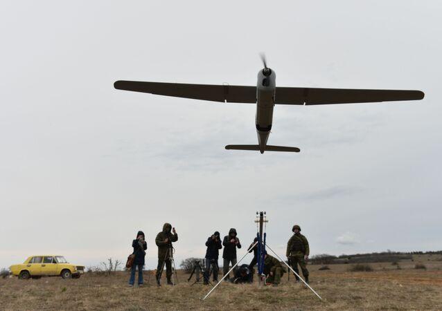 Engenheira de uma unidade feminina de controle de drones da brigada de reconhecimento da Frota do Mar Negro lançando o veículo aéreo não-tripulado Orlan-10 durante um treinamento