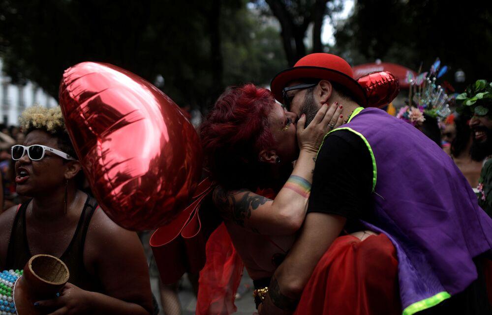 Casal se beija em meio à folia do bloco Calcinhas Bélicas durante as festas do pré-carnaval do Rio de Janeiro